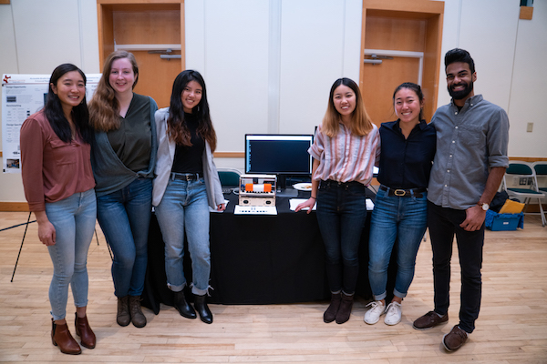 A team of students pose in front of their table.