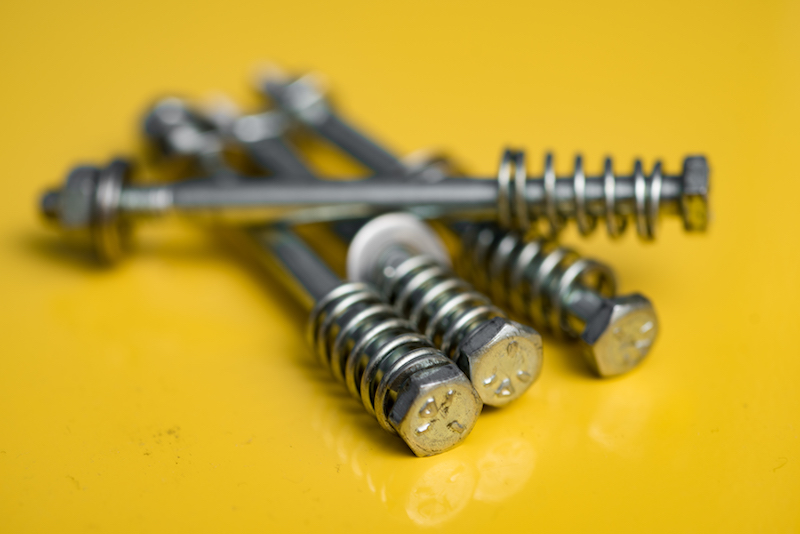 metal screws on a yellow background