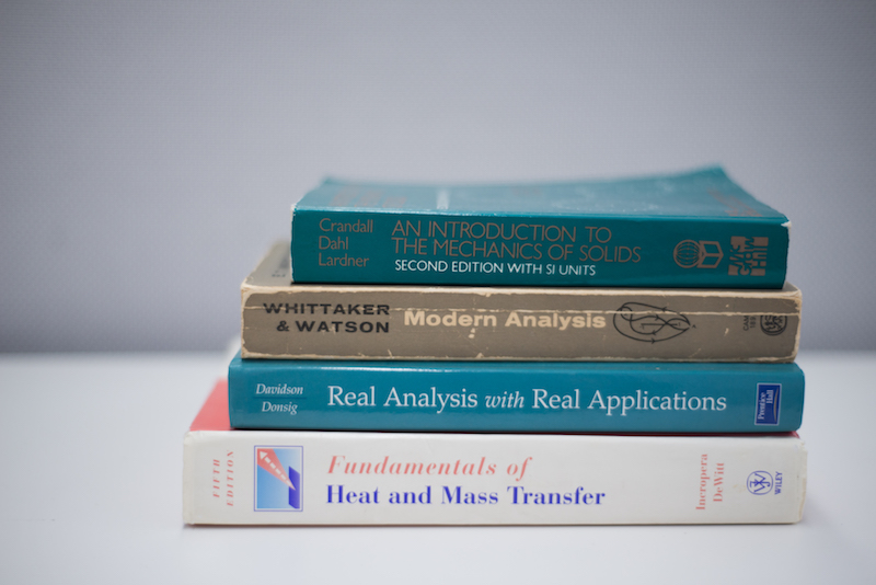 Stack of textbooks: An introduction to the mechanics of solids, Modern Analysis, Real Analysis with Real Applications, Fundamentals of Heat and Mass Transfer